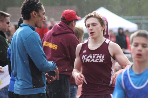 Senior Marcus Martin is greeted by teammate T. McBurnette after a race Saturday.